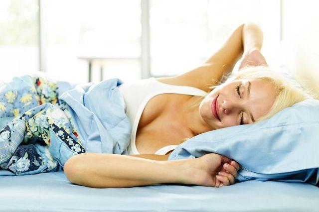 Женщина нежится в кровати
